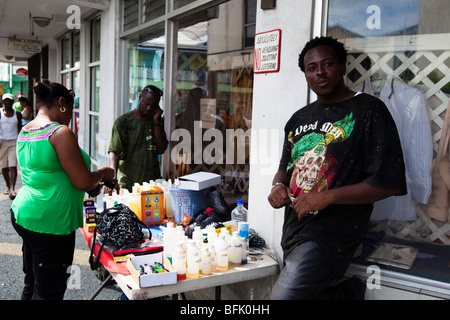 Black man from Antigua selling household goods from a stall at a street corner in St Johns town. - Stock Photo