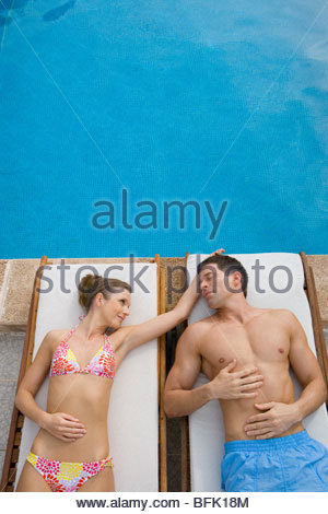 Couple laying on lounge chairs at poolside - Stock Photo