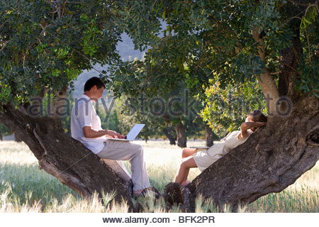 Couple with laptop laying against tree - Stock Photo