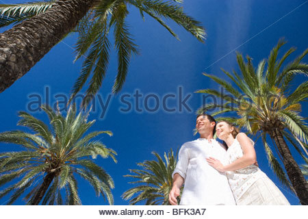 Smiling couple hugging under palm trees - Stock Photo