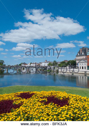 View of town and bridge spanning river on sunny day - Stock Photo