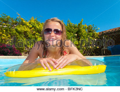 Portrait of smiling teenage girl laying on pool raft in swimming pool - Stock Photo