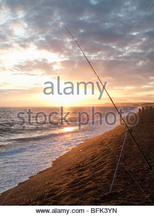 Tranquil sun setting on horizon over ocean with fishing rod in foreground - Stock Photo