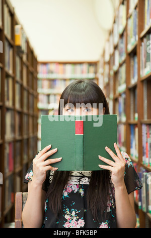 Asian woman reading book in library