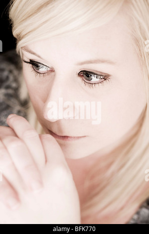 Portrait of blond woman thinking - Stock Photo