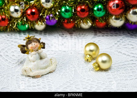 Christmas decoration angel figurine with colorful baubles - Stock Photo