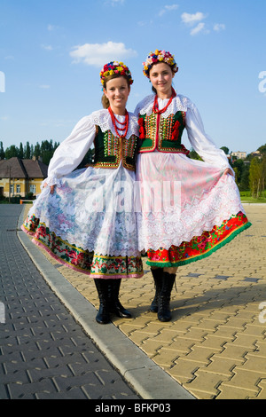 Two young women wearing national costume, near the Polish city of Krakow. Poland. - Stock Photo