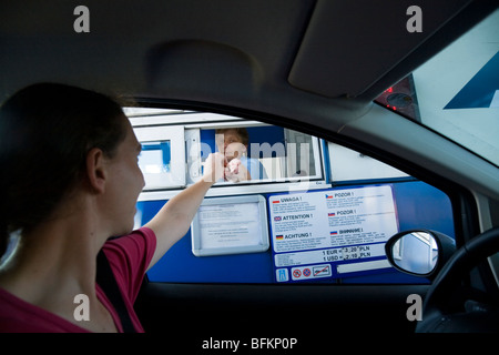 Tourist driver pays a road toll at a Polish motorway toll booth. Near Krakow, Poland. - Stock Photo