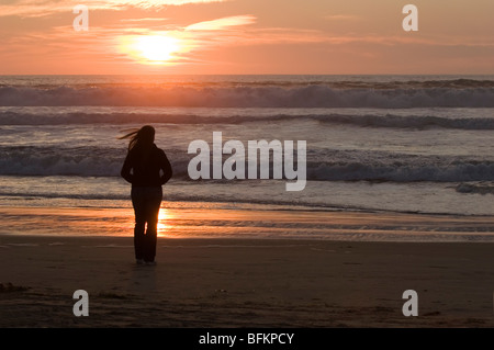 An anonymous woman seen in silhouette standing on a beach at sunset, her hair blowing in the wind. - Stock Photo