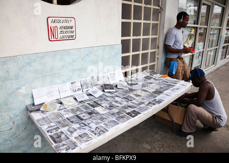 Illegal vendor selling bootleg CDs and Videos from a stall in St Johns town, Antigua, West Indies - Stock Photo
