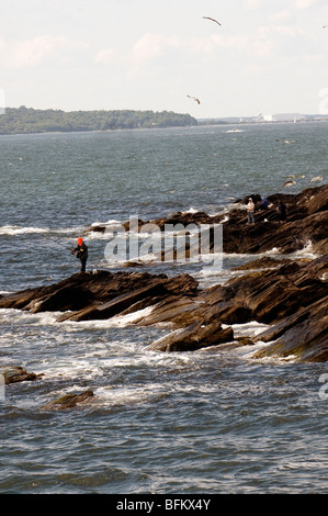 Solitary fisherman on rocks off beavertail on Jamestown Rhode Island - Stock Photo