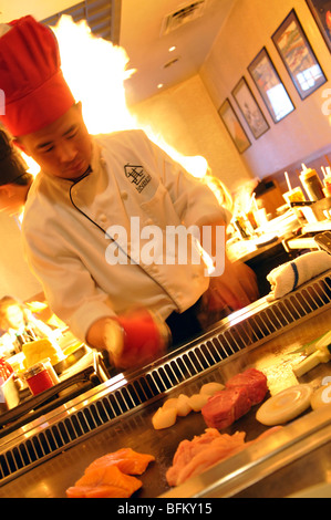 Chef cooking food on a grill at Japanese restaurant - Stock Photo