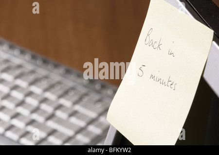 Sticky note with 'Back in five minutes' written on it - Stock Photo