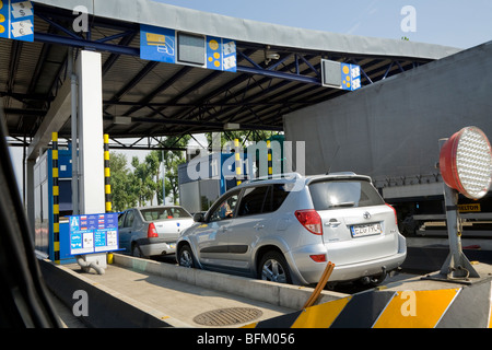 Car and other vehicles approach a Polish motorway toll booth. Near Krakow, Poland. - Stock Photo
