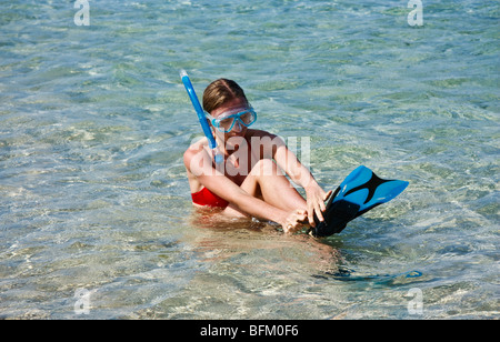 Young woman wearing snorkeling gear is putting on the fins, sitting in the ocean about to swim - Stock Photo