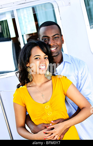 Portrait of young romantic couple hugging in front of yacht - Stock Photo