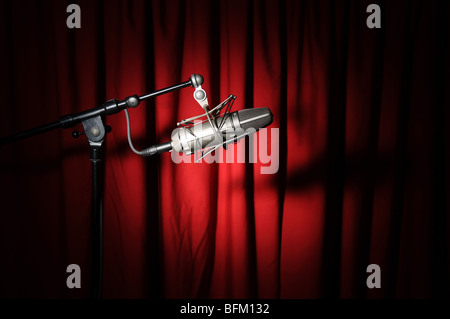 Vintage microphone with spotlight over a red curtain - Stock Photo