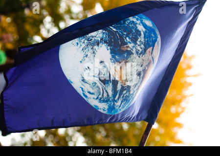 A blue flag with an image of plant earth flies over an environmental protest event. - Stock Photo