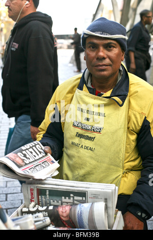 good humored dark skinned man selling the New York Post newspaper on the plaza at Bowling Green in Lower Manhattan - Stock Photo