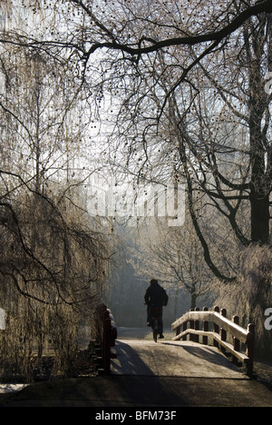 Cyclist crossing a bridge in Oosterpark on a winter morning. Amsterdam, The Netherlands - Stock Photo