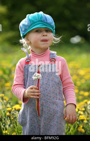 little girl in blue cap on a beautiful summer meadow - Stock Photo