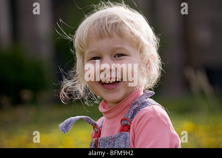 smiling little girl on a beautiful summer meadow background - Stock Photo