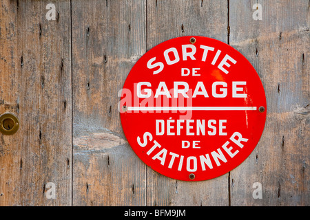 French Red 'Garage Exit/No Parking' Sign on Wooden Door. - Stock Photo