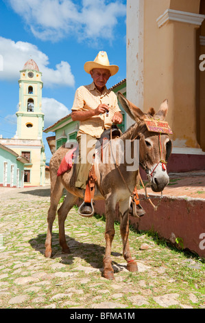 Man on Donkey smoking a cigar in Trinidad, Cuba - Stock Photo