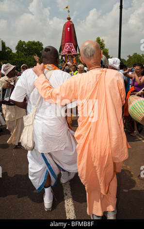 Two Hare Krishna devotees attend the celebrations of Ratha Yatra  The Hindu festival of chariots in London UK - Stock Photo