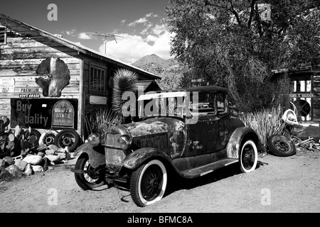 Old looking black and white photo of an old worn car wreck in a rural desert junkyard environment by a shack with - Stock Photo