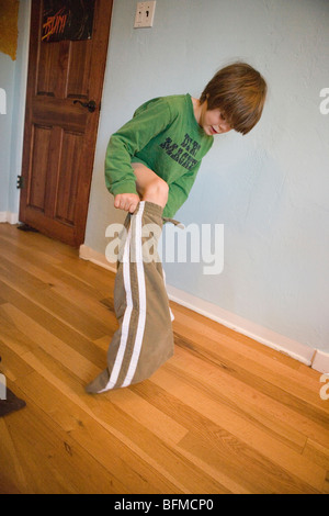 Seven year old boy getting dressed in the morning, putting on his pants, getting ready for school. - Stock Photo