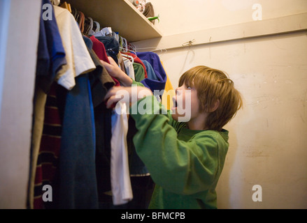 Seven year old selecting clothes to wear inside his closet in the morning - Stock Photo