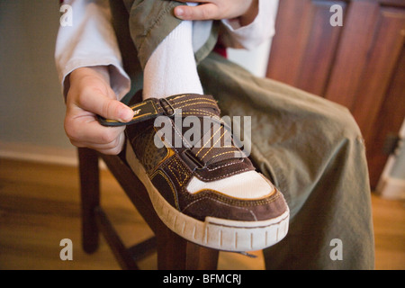 Close up of a child putting on his sneakers using a velcro strap, getting dressed - Stock Photo