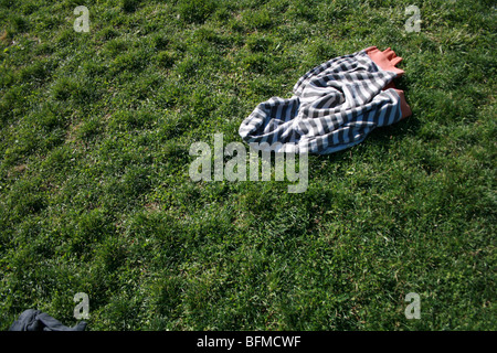a jacket left laying in a grassy field - Stock Photo