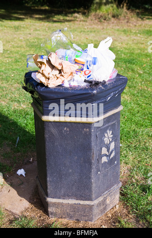 A rubbish bin in a public park overflowing with general rubbish and plastic containers. Dorset. England. UK. - Stock Photo