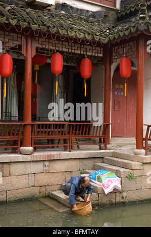 Man cleaning things in a basket. Tongli, China. - Stock Photo
