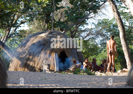 Namibia, Bushmanland. A group of Bushman (or San) villagers outside their grass-thatched shelter in the village - Stock Photo