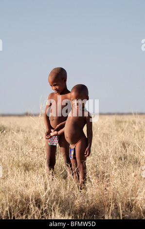 Botswana, Makgadikgadi. Bushmen children standing in the dry grasses of the Kalahari - Stock Photo