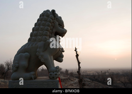 China, Ningxia Province, Baishikou near Yinchuan, lion statue at sunrise - Stock Photo