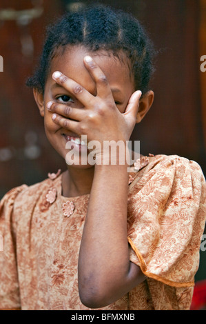 Tanzania, Zanzibar, Stone Town. A happy young girl with her hand to her face in Stone Town. - Stock Photo