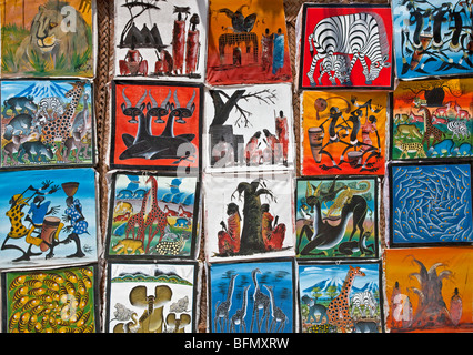 Tanzania, Zanzibar. Colourful paintings by local artists on sale near Paje Beach in the southeast of the island. - Stock Photo