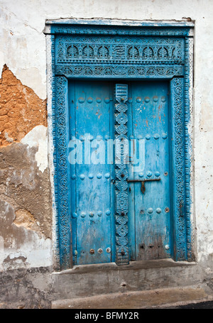 Tanzania, Zanzibar, Stone Town. A painted carved wooden door of a house in Stone Town. - Stock Photo