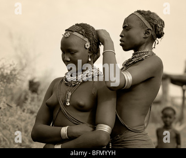 Ethiopia, Omo Delta.  A Dassanech girl braids her sister's hair at her village in the Omo Delta. - Stock Photo