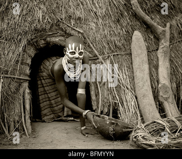 Ethiopia, Omo Delta.  A young Karo girl holds a calabash in the doorway of her hut in the village of Duss. - Stock Photo