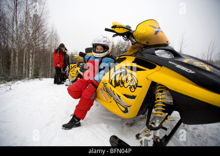 Finland, Pielinen region of North Koralia in Finnish Lapland. Girl on snowmobile (or skidoo) safari. (MR) - Stock Photo