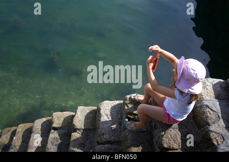 France, Brittany. A young girl catching crabs from harbour steps in La Trinite sur Mer. (MR) - Stock Photo