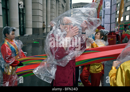 a man trying to put on  a rain cape during the 2009 lord mayor's parade in london - Stock Photo