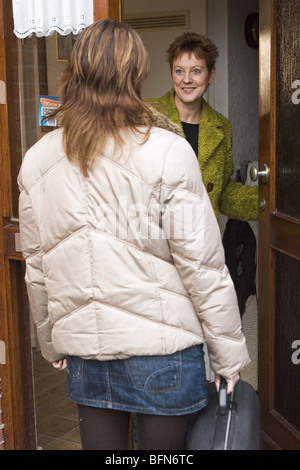 Student comes home talking on doorstep -  woman answering door  SerieCVS417015 rear view - Stock Photo