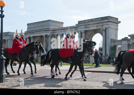 Guards in red tunics and plumed helmets ride in front of arches at Hyde Park corner - Stock Photo