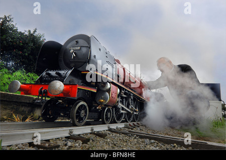 A model railway enthusiast with a hand built steam model of a Stanier LMS Coronation Class 4-6-2 pacific steam locomotive. - Stock Photo